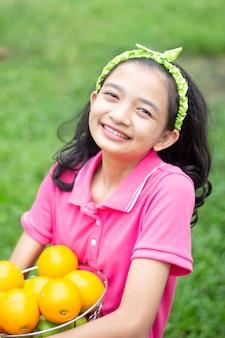 庭のオレンジ色のバスケットを持つ幸せなlittelアジアの女の子。