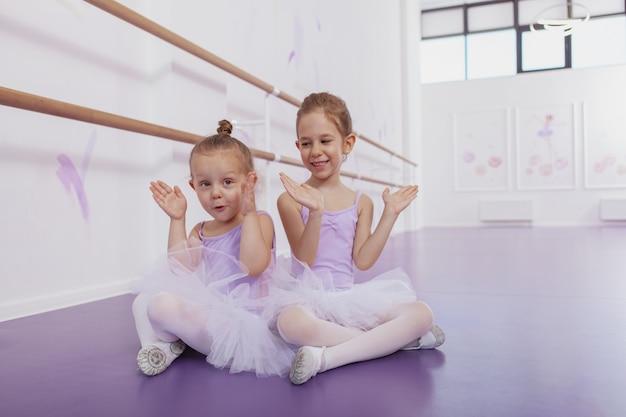 Счастливые маленькие очаровательные девочки в купальниках и юбках-пачках веселятся вместе на уроках танцев