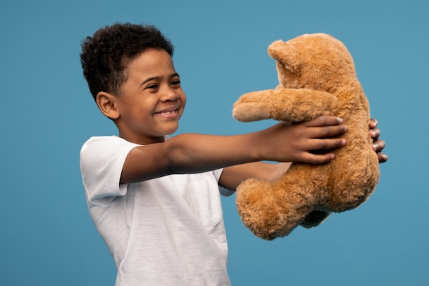 Счастливый маленький африканский мальчик с большим красным спелым яблоком в руке, указывая на плод и глядя на вас, рекомендуя его как здоровую пищу