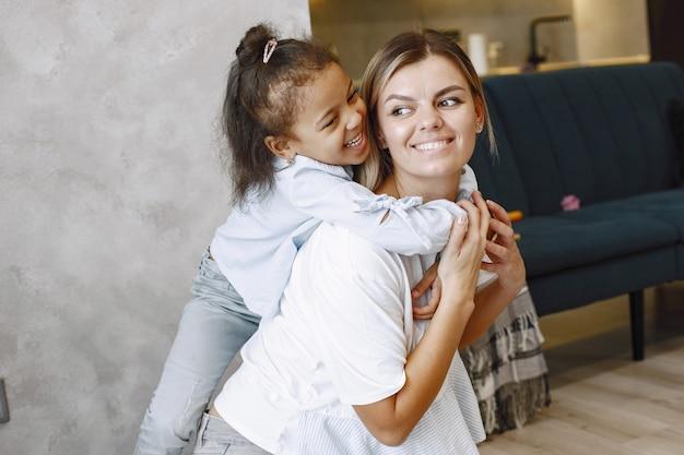 笑顔の金髪の母親の肩越しに登る幸せな小さなアフリカ系アメリカ人の女の子。母と娘が抱きしめます。