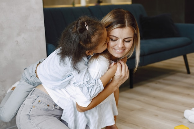 Happy little afro-american girl climbing over the shoulders of smiling blonde mother. mother and daughter hugging