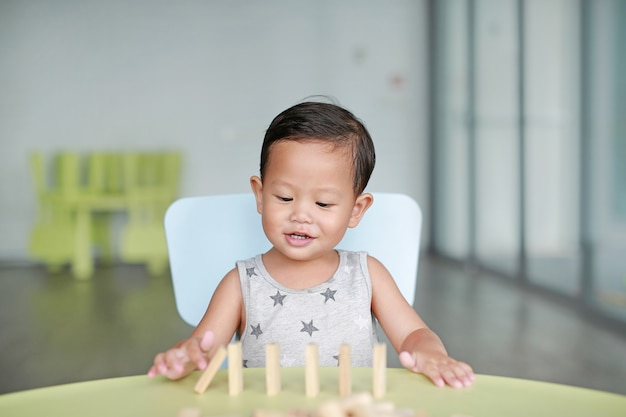Happy little asian baby boy playing wood blocks tower game for brain and physical development skill in a classroom. focus at children face. kid imagination and learning concept.
