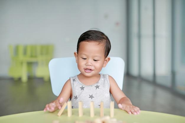 행복 한 작은 아시아 아기 나무 블록 탑 교실에서 두뇌와 물리 개발 기술에 대 한 타워 게임. 어린이 얼굴에 중점을 둡니다. 아이의 상상력과 학습 개념.