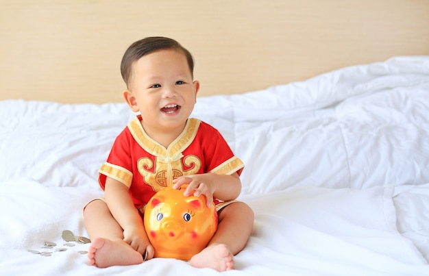 Happy little asian baby boy in traditional chinese dress with a piggy bank on bed.