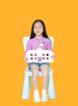 Happy little asian child girl holding paper school sitting on kid chair