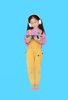 Happy little asian child girl in pink-yellow dungarees with headphones to enjoys listening music