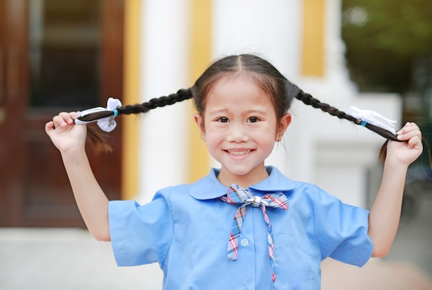 Happy little asian child girl in school uniform holding her two tied ponytails hairs.