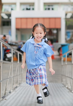 Happy little asian child girl in school uniform running up metal stair.