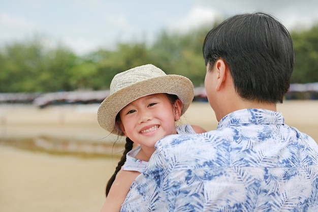 Happy little asian child girl with his father carries on the beach.