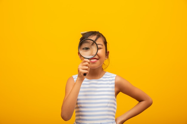 Happy little asian child with magnifying glass