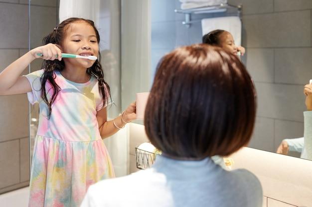 Счастливая маленькая азиатская девочка чистит зубы в ванной и смотрит на мать