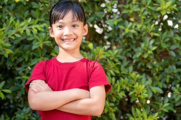 큰 미소와 웃음으로 앞니를 보여주는 행복 한 작은 아시아 여자 아이: 건강 한 행복 웃 고 웃는 얼굴 젊은 사랑 스러운 사랑 스러운 여자 아이입니다. 아시아 초등학교 학생의 즐거운 초상화.
