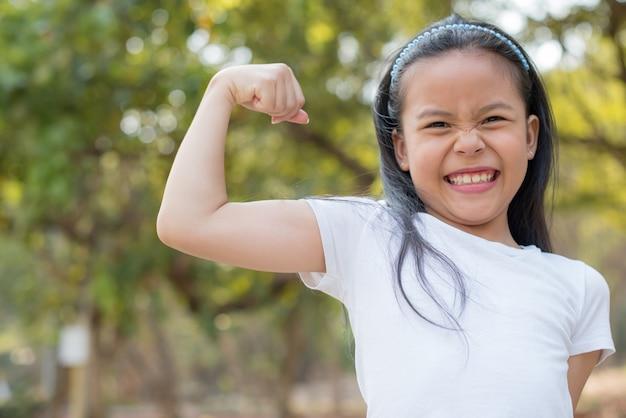 幸せな小さなアジアの女の子の子供が大きな笑顔で前歯を見せて立っています。腕の筋肉を誇らしげに笑って、上腕二頭筋を見せています。フィットネスのコンセプト。