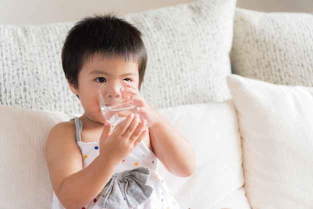 Happy little asian girl hand holding drinking water glass