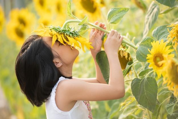 Felice bambina asiatica divertendosi tra i girasoli fioriti sotto i dolci raggi del sole.