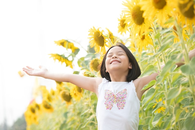 Happy little asian girl having fun among blooming sunflowers under the gentle rays of the sun.