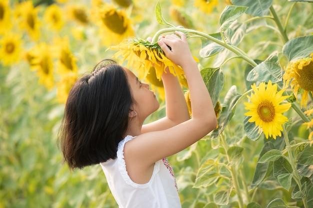 태양의 부드러운 광선 아래 개화 해바라기 가운데 재미 행복 아시아 소녀.