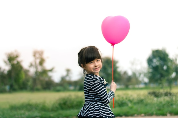 Happy little asian girl holding pink balloon in hand