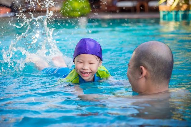 Счастливая маленькая азиатская девушка учится плавать с отцом в бассейне