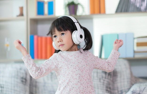 Happy little asian girl listening to music