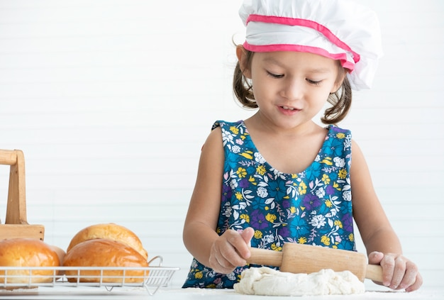 Happy little asian girl making a dough