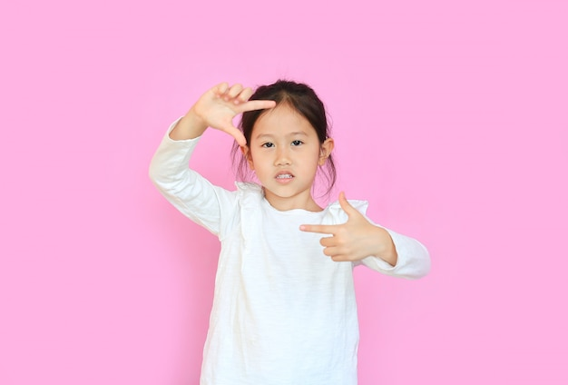 Happy little asian girl on pink background