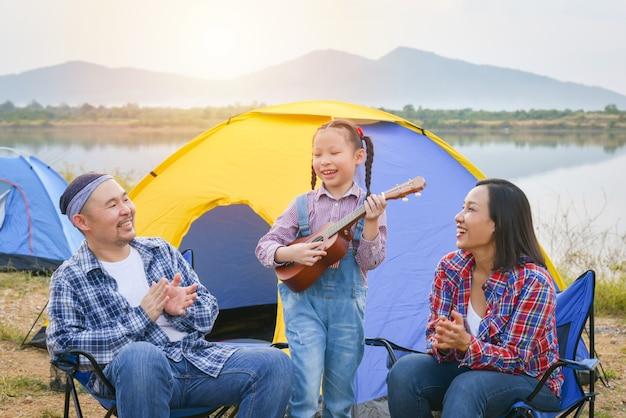 Счастливая маленькая азиатская девочка играет на гавайской гитаре и ее родители хлопают в ладоши в кемпинге