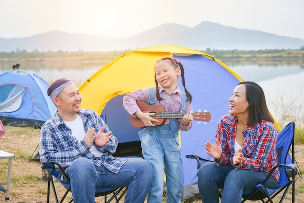 Happy little asian girl playing ukulele and her parents clapping hands at camping site