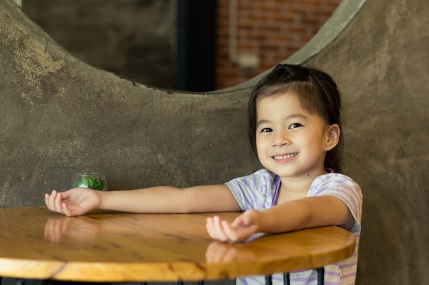 Happy little asian girl put hands on table waiting for snack, selective focus.