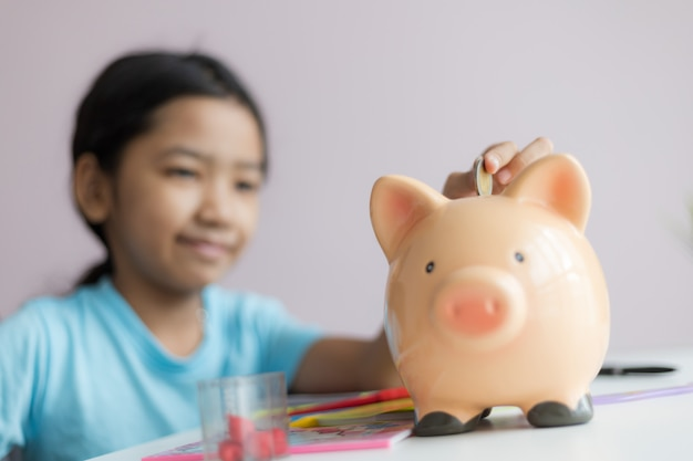 Happy little asian girl putting money coin into piggy bank