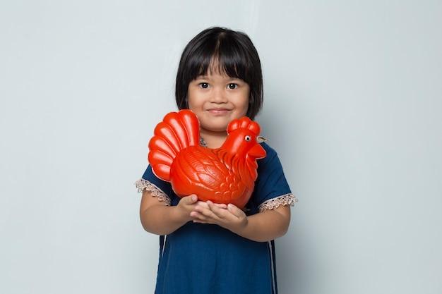 白い背景で隔離の鶏の銀行でお金を節約する幸せな小さなアジアの女の子