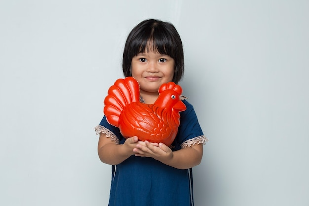 Happy little asian girl saving money with a chicken bank isolated on white background
