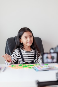 Счастливая маленькая азиатская девушка сидит за белым столом и транслируется в прямом эфире для социальных сетей со счастьем с помощью камеры выберите фокус малая глубина резкости