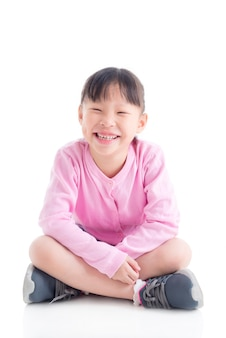 Happy little asian girl sitting and smiling over white space