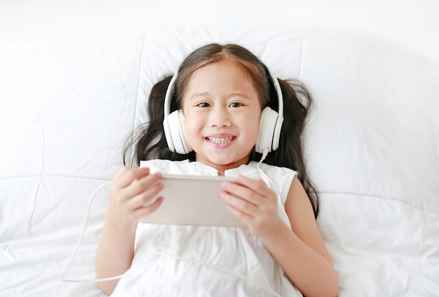 Happy little asian girl using headphones listen music by smartphone smiling and looking camera.