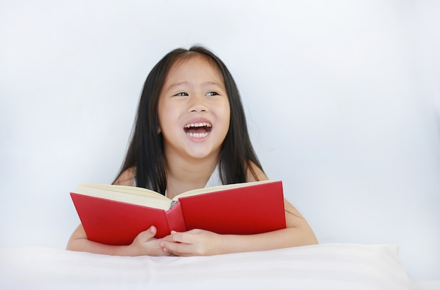 Happy little asian kid girl reading hardcover book lying with pillow on bed against white background.