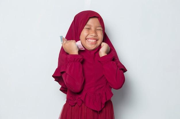 Счастливая маленькая азиатская мусульманская девушка держит деньги на белом фоне