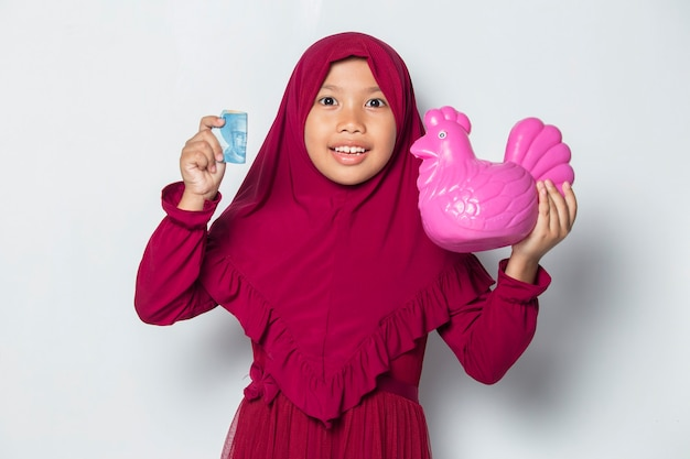 Happy little asian muslim girl saving money with a chicken bank isolated on white background