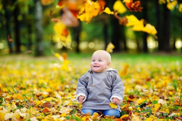 Happy little baby boy having fun in the autumn park