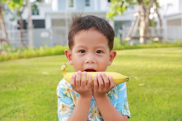 Счастливый маленький мальчик держит желтый банан в саду природы