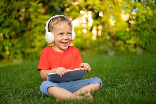 笑顔の公園で屋外のタブレットコンピューターを保持しているワイヤレスヘッドフォンで幸せな小さな男の子