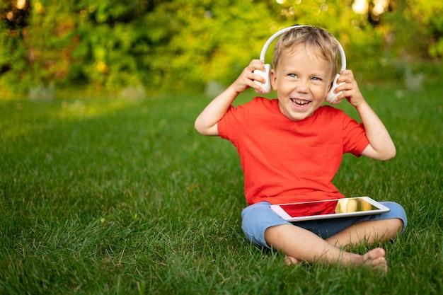夏の公園で屋外でタブレットコンピューターを保持しているワイヤレスヘッドフォンで幸せな小さな男の子