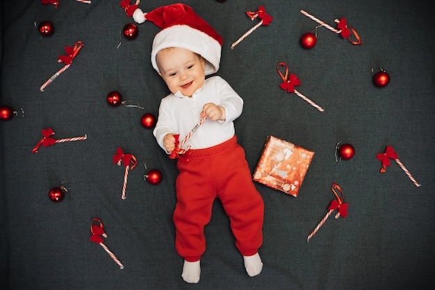 Happy little baby boy in santa claus hat smiling among christmas candy canes