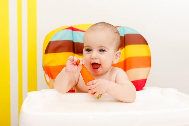 Счастливый маленький ребенок ест морковь