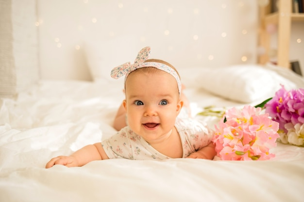 Счастливая маленькая девочка лежит в красочном боди и ободке на белом одеяле с цветами