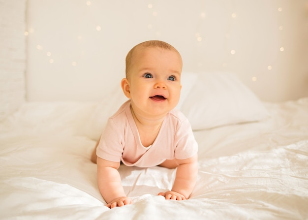 Happy little baby girl in a pink bodysuit is onll fours on the bed