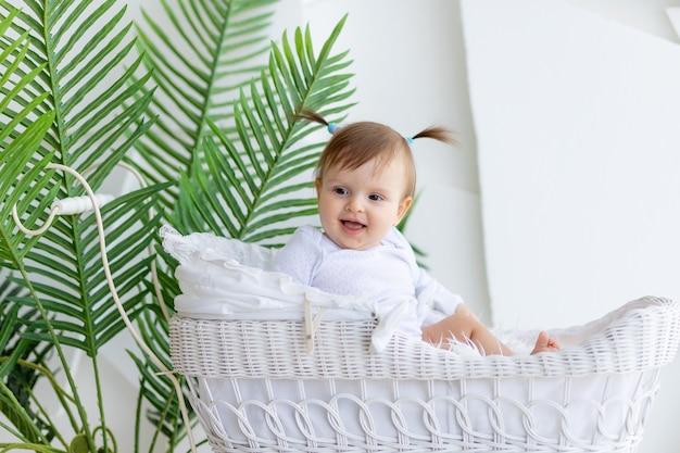 Счастливая маленькая девочка сидит в красивой коляске в белом боди дома