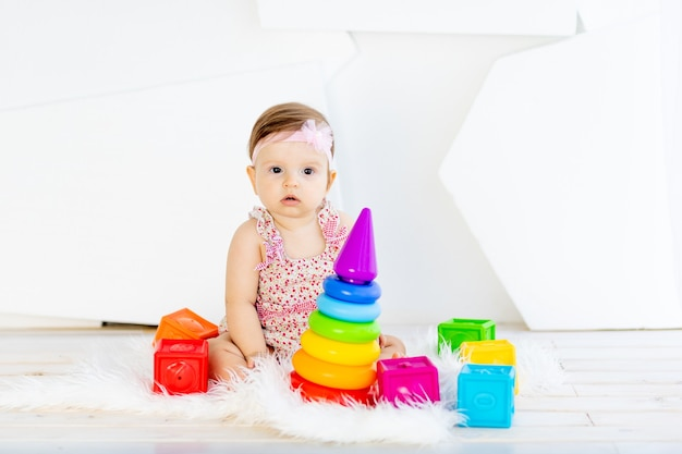 밝은 장난감으로 빨간 드레스에 흰색 방에 앉아 행복 한 작은 아기 소녀