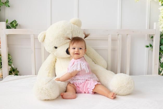 Счастливая маленькая девочка сидит на белой кровати в розовой одежде
