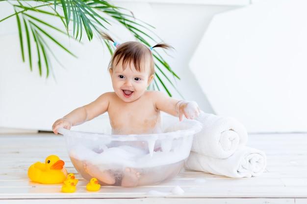 행복한 아기 소녀는 집에서 밝은 방에서 거품과 물로 분지에서 씻어서 재생합니다.